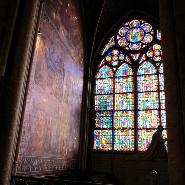 A statue in silhouette in front of a stained glass Notre-Dame window