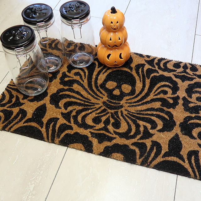 A skull-patterned coir doormat, a ceramic pumpkin stack ornament and some black-lidded mason jars with a skull-and-crossbones motif