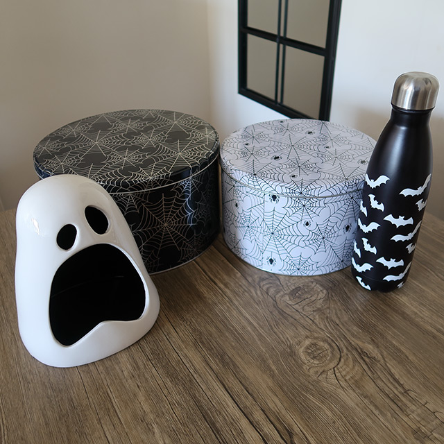 Halloween spiderweb-patterned cake tins, a bat-patterned water bottle and ghost-shaped candy bowl