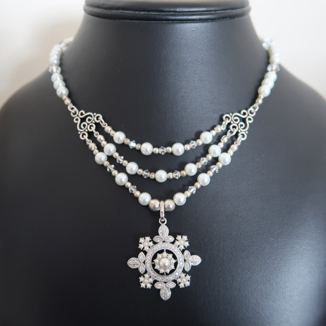 A white glass pearl and Swarovski crystal necklace with a snowflake pendant