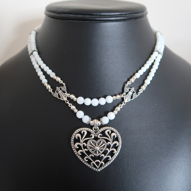 A white mother-of-pearl beaded necklace with a filigree heart pendant