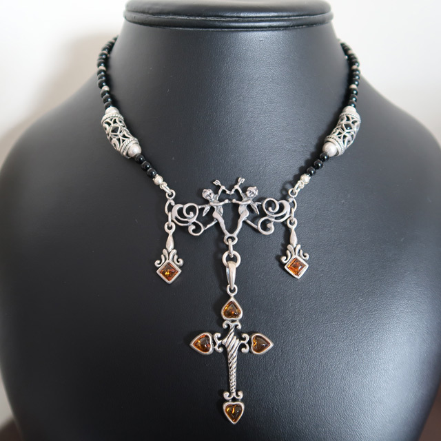 A black onyx beaded necklace with an amber cross pendant